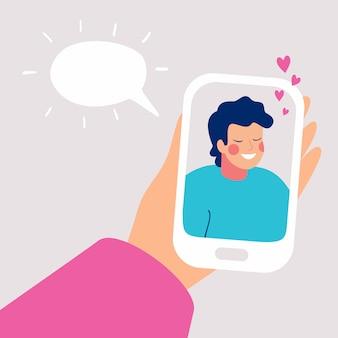 人間の手は、ディスプレイ上の笑顔の若い男とモバイルのスマートフォンを保持します。