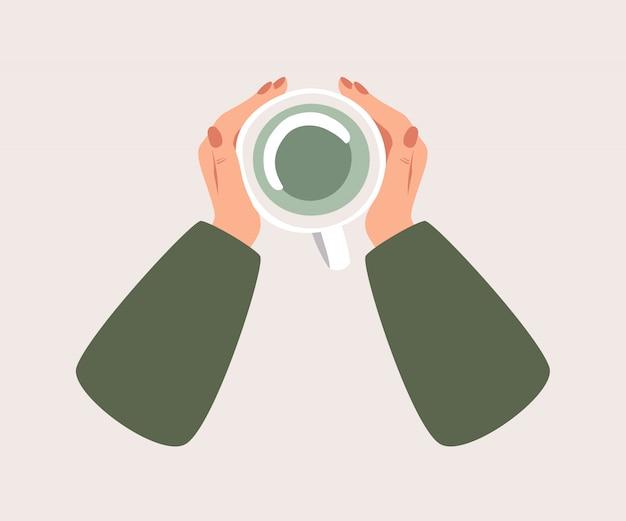 Вид сверху на чашку зеленого чая греет руки человека.