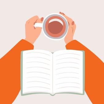 一杯のコーヒーまたは紅茶と開いた本を保持している女性の手がトップビュー