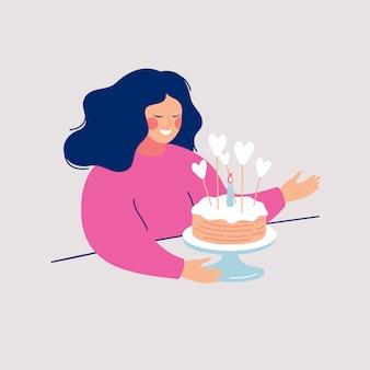 Счастливая молодая женщина собирается съесть вкусный пирог, украшенный глазурью, сердца и одна горящая свеча.