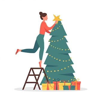 Милая женщина, украшающая рождественскую елку гирляндами и золотой звездой.