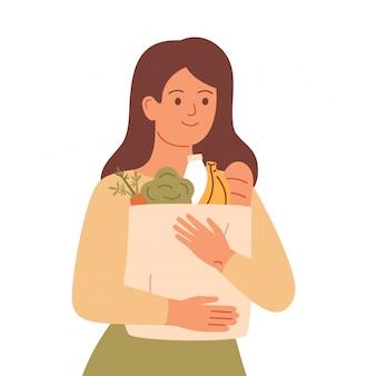 少女は、天然物と食料品の袋を保持しています。健康的な食事のコンセプト、廃棄物ゼロ、持続可能なライフスタイル