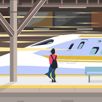 Вид сзади на молодая женщина ждет поезд метро