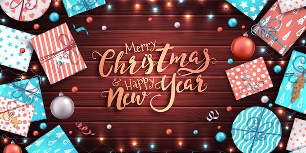 メリークリスマスの背景。カラフルなギフトボックス、クリスマスつまらないもの、花輪