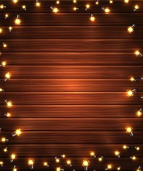 木製の背景のライトのクリスマスガーランド