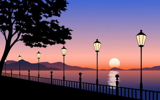 Закат на берегу реки с уличными фонарями