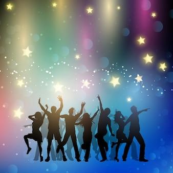 星と踊る人々のシルエット