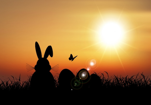 イースターのバニーは夕日の空に対して芝生で座っていた