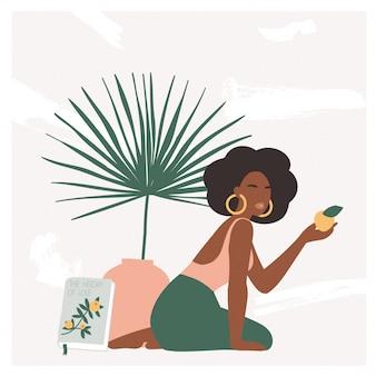 Красивая богемная женщина, сидя на полу в современном интерьере с ваза и пальмовых листьев.