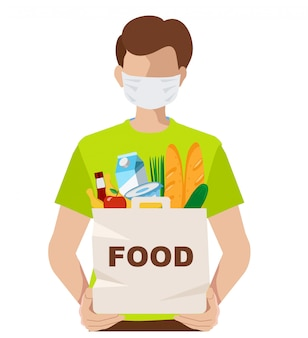 フードパッケージと医療マスクのボランティア。コロナウイルスの蔓延を防ぐために医療用マスクを身に着けている若い男。人は食料品を袋に入れています。