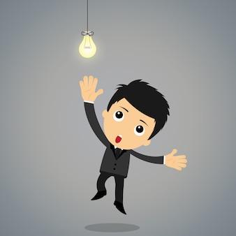 アイデア電球をつかむことを試みるまで達するビジネスマン。