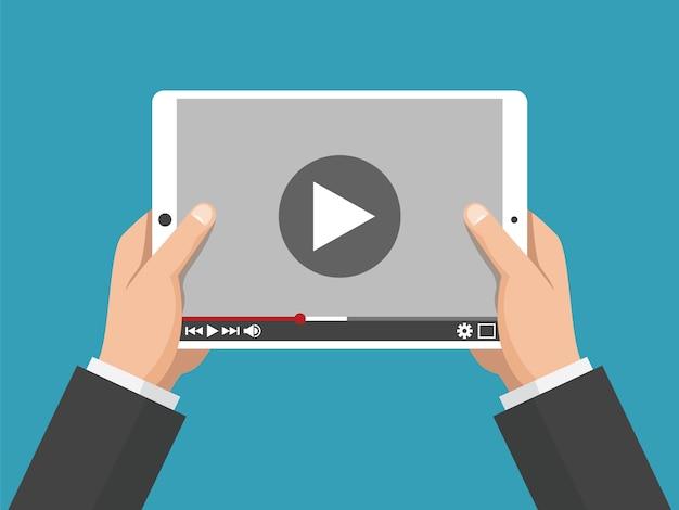 Руки держат белый планшетный компьютер с видеоплеером на экране
