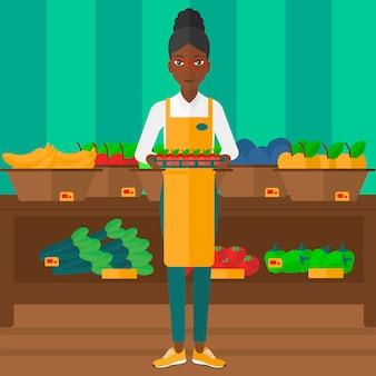 Работник супермаркета с коробкой, полной яблок
