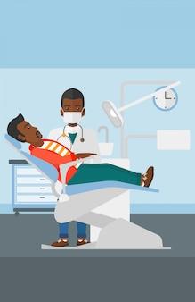 Стоматолог и человек в кресле стоматолога.