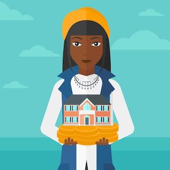 家のモデルを保持している女性。