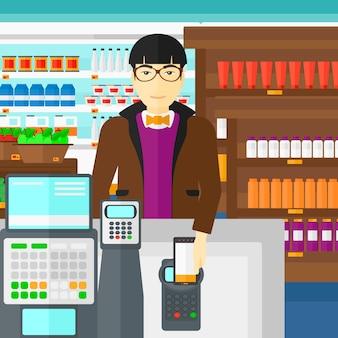 端末を使用してスマートフォンで支払う顧客。