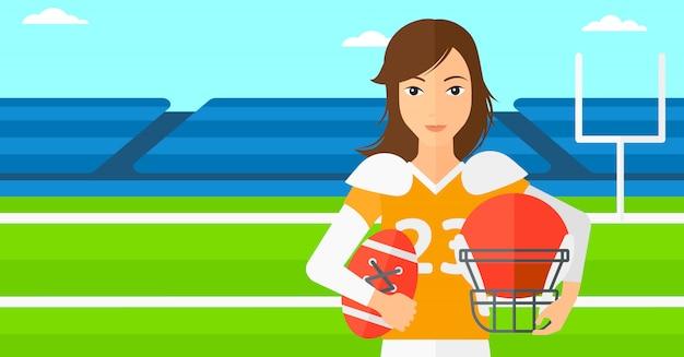 Игрок в регби с мячом и шлем в руках.