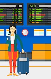 女性のスーツケースに立って、チケットを保持