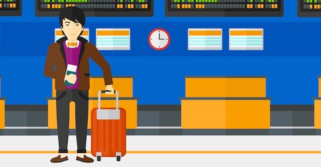 スーツケースに立って、チケットを保持している男
