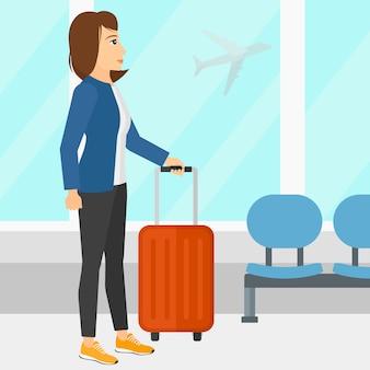 Женщина в аэропорту с чемоданом