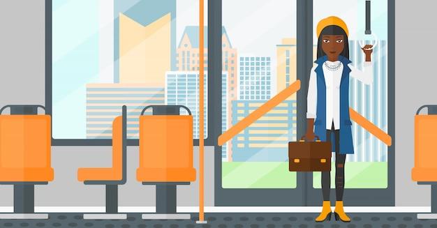 公共交通機関の中に立っている女性。