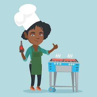 Африканская женщина приготовления стейка на гриле.