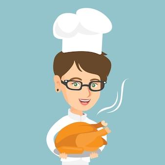 Кавказский шеф-повар держит жареную курицу.