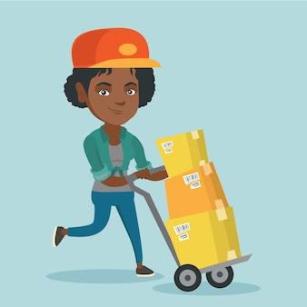 Женщина-почтальон толкает тележку с посылками.