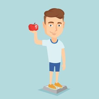 スケールの上に立って、手にリンゴを保持している男。