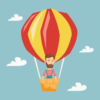 若い男が熱気球で飛んでいます。
