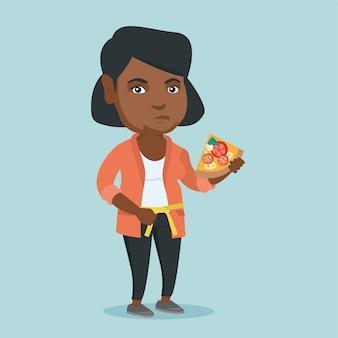 Толстая африканская женщина с пиццей измеряет талию