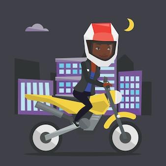 夜にバイクに乗る女性。