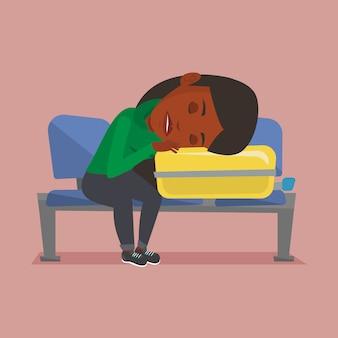 Вымотанная женщина спать на чемодане на авиапорте.