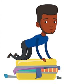 Молодой человек пытается закрыть чемодан.