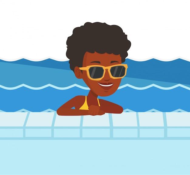 スイミングプールで笑顔の若い女性。