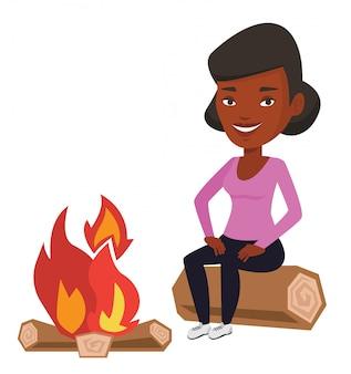 キャンプでキャンプファイヤーの近くのログに座っている女性。