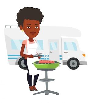 キャンピングカーの前でバーベキューを持つ女性。