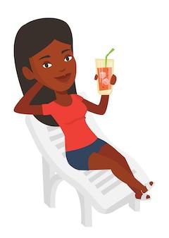 Женщина расслабляющий на шезлонге.