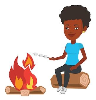 女性はキャンプファイヤーでマシュマロを焙煎します。