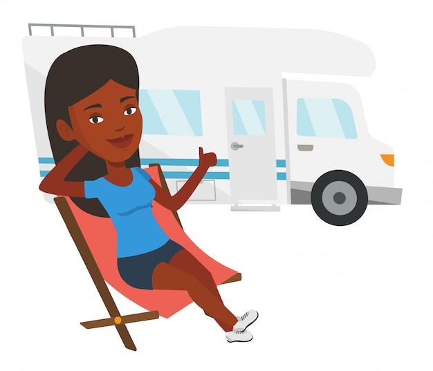 キャンピングカーの前の椅子に座っている女性。
