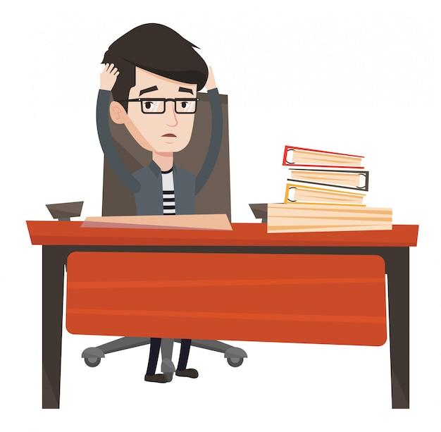 Напряженный работник сидит на рабочем месте.