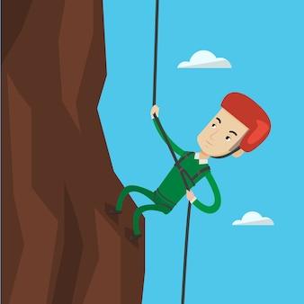 ロープで山に登る男。