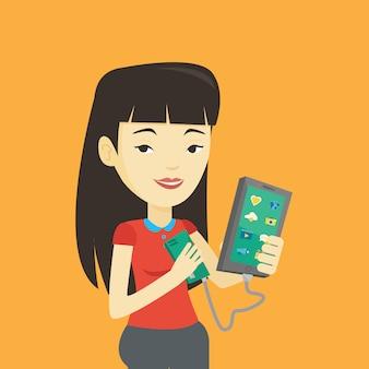 Женщина перезаряжает смартфон от портативного аккумулятора.