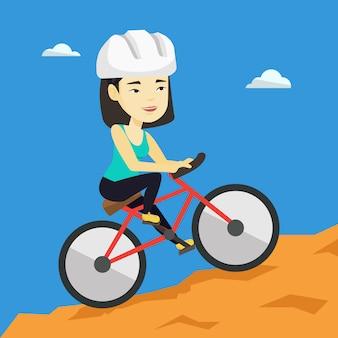 山を旅行する自転車の若い女性。