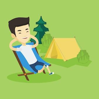 Человек сидит в раскладное кресло в лагере.