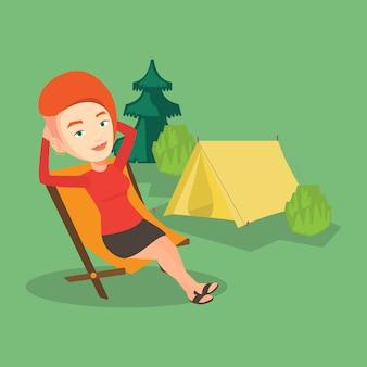 Женщина сидит в раскладном кресле в лагере.