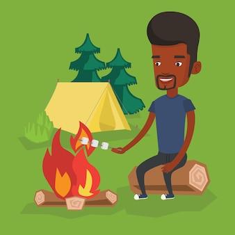 キャンプファイヤーでマシュマロを焙煎する男。