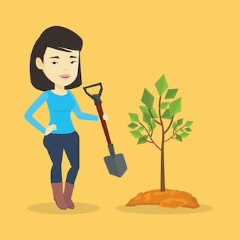Женщина сажает дерево.