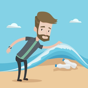 海の波の下でペットボトルを示す男。