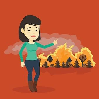 Женщина, стоящая на фоне лесного пожара.